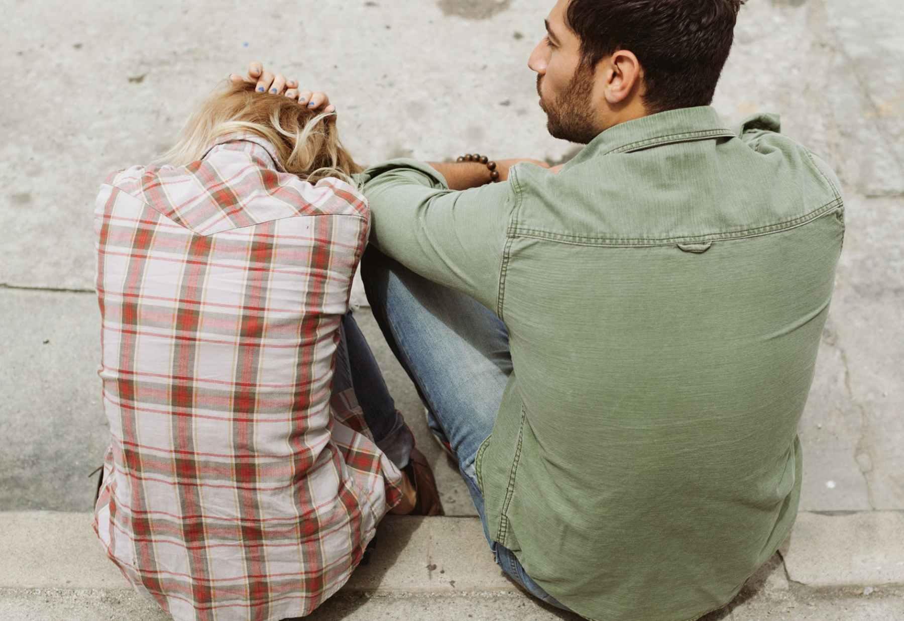 man and woman sitting on sidewalk